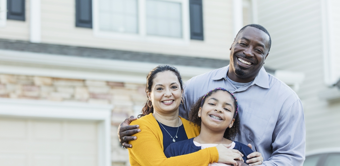 Diverse family of mother, father, daughter in front of single family home